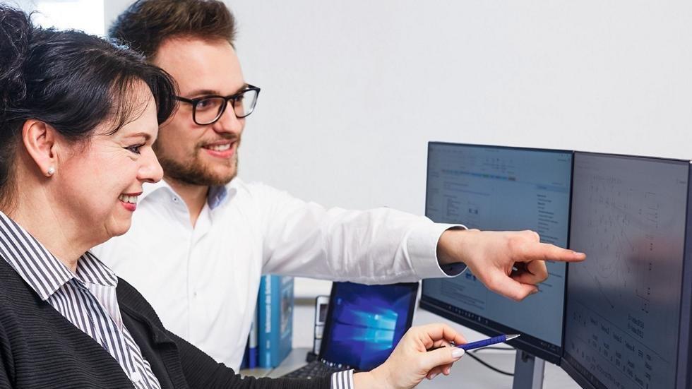 Mann und Frau analysieren am Bildschirm